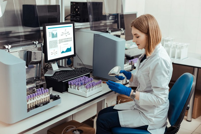 woman in lab working with barcode scanner and vials