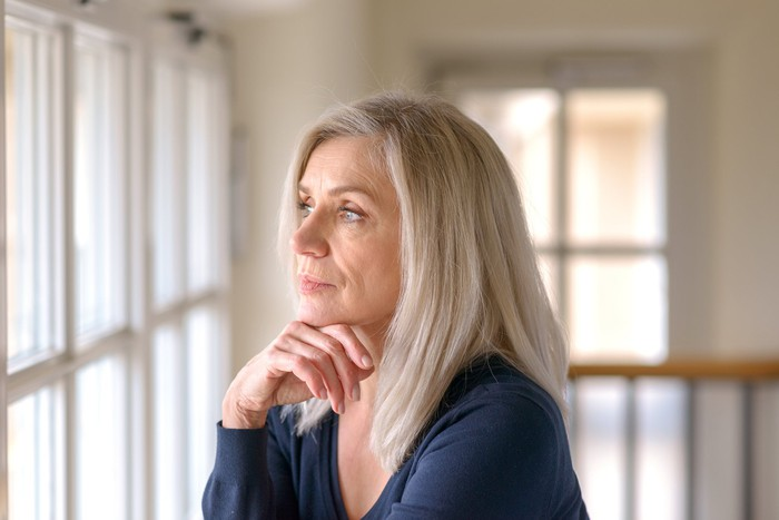 Older woman looking concerned and staring out the window