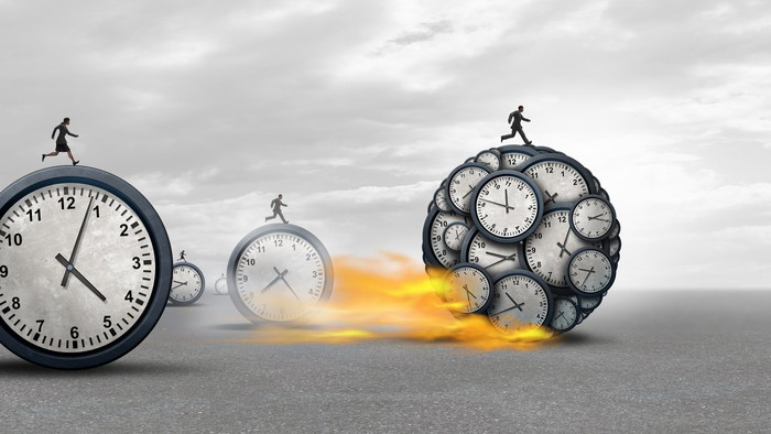 small stick figures race on large balls made of clocks with one with many clocks within it blazing ahead of the others.