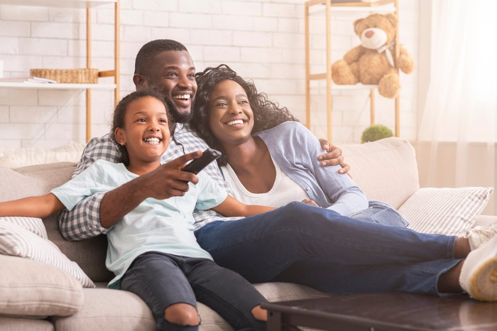 A family sits together on the couch and smiles at what they are seeing on a nearby TV screen.