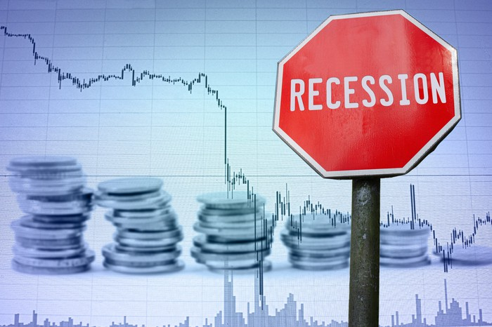 """Red """"recession"""" sign in front of a chart with a declining line."""