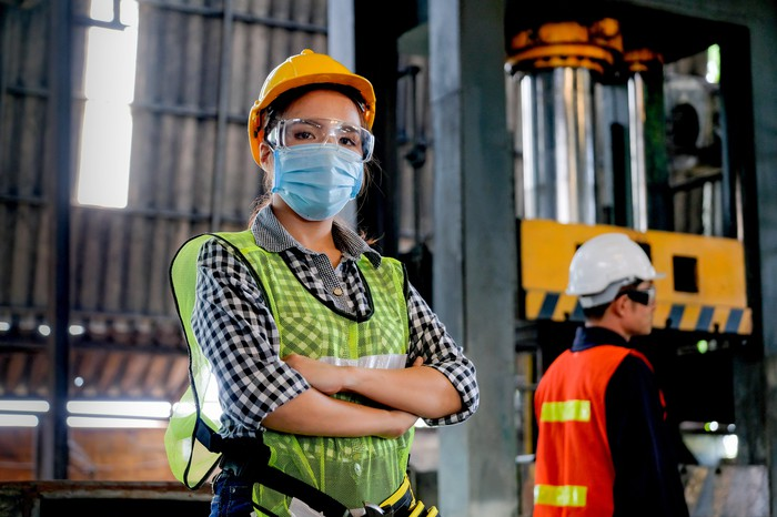 Factory worker with hygienic mask stand with confident action with her co-worker in the background.