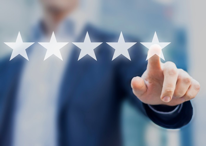 Businessman pointing to one of five stars