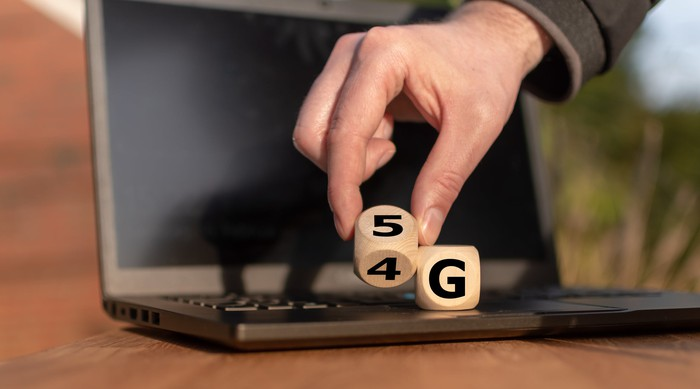 "Wooden blocks reading ""5G"" placed on a laptop."