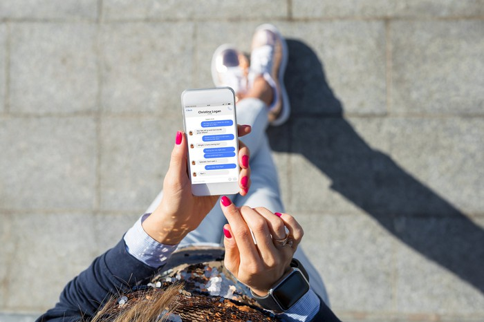 A woman types a text message on a smartphone.