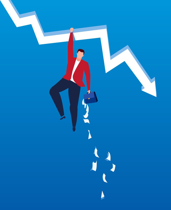 A man clings to a downward sloping arrow as files fall out of his briefcase.