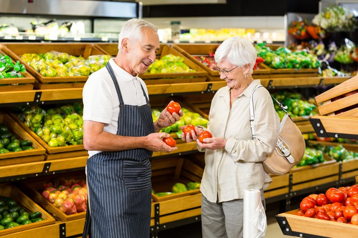 Older man in apron and older woman in supermarket holding tomatoes
