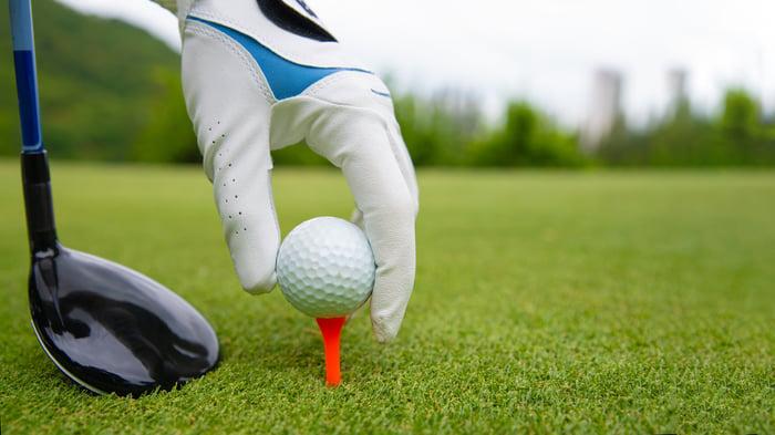 Golfer placing a golf ball on a tee.