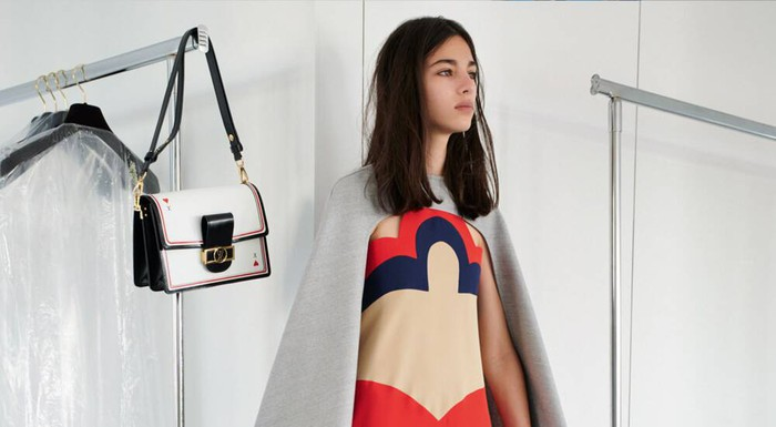 A model wearing a Louis Vuitton dress and leather handbag hanging on a rack next to her.