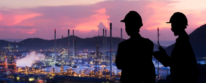 Workers look over an oil refinery site at sunset