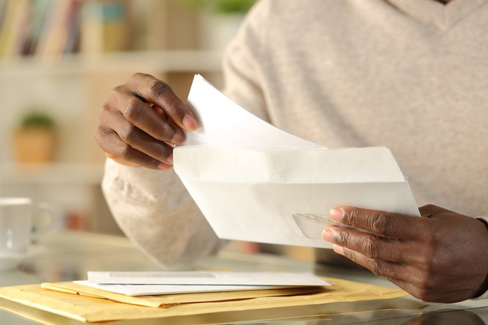 A man stuffing a letter in an envelope.
