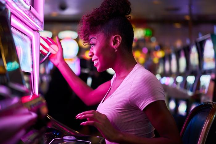 A woman plays a slot machine.