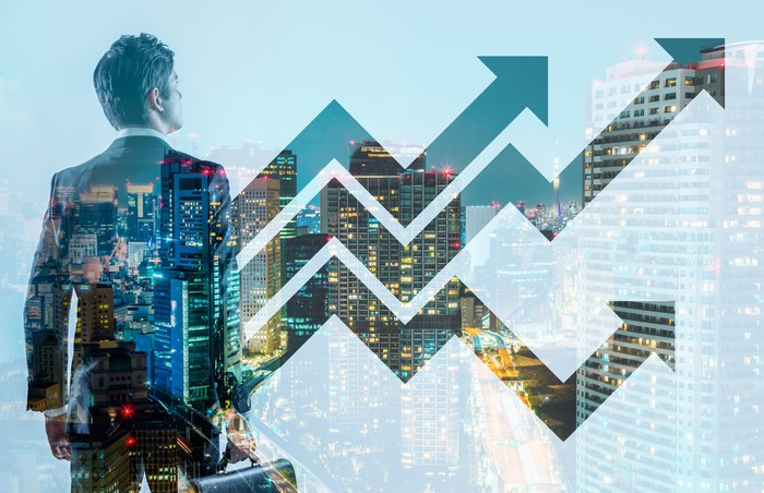 A man in a business suit looking at increasing arrows on a graph, overlaid on a cityscape.