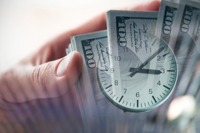 A clock superimposed atop a stack of one hundred dollar bills that are being held in a hand.
