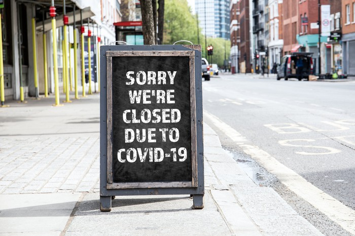A sign in front of a retail store that reads, Sorry We're Closed Due to COVID-19.