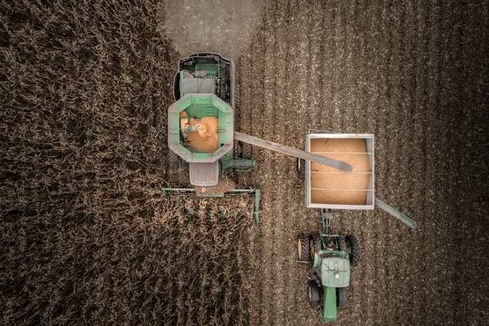 An overhead view of a tractor and combine moving through a corn field.