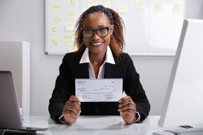Smiling professionally dressed woman holding a check