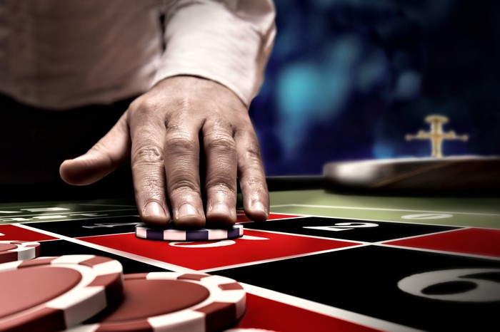 Gambler betting by placing a chip on a roulette table