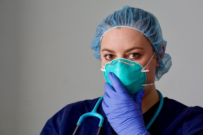 Healthcare professional holding gloved hand up to her face mask