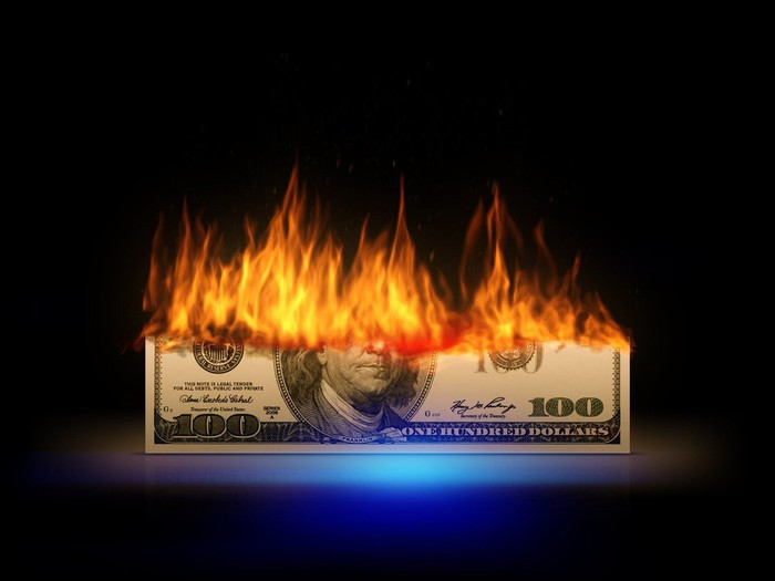 Bottom half of a $100 bill lit on fire.