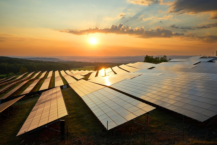 Solar panels with the sun setting in the background.