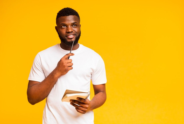 A young man thinks while holding a notepad against an orange background.