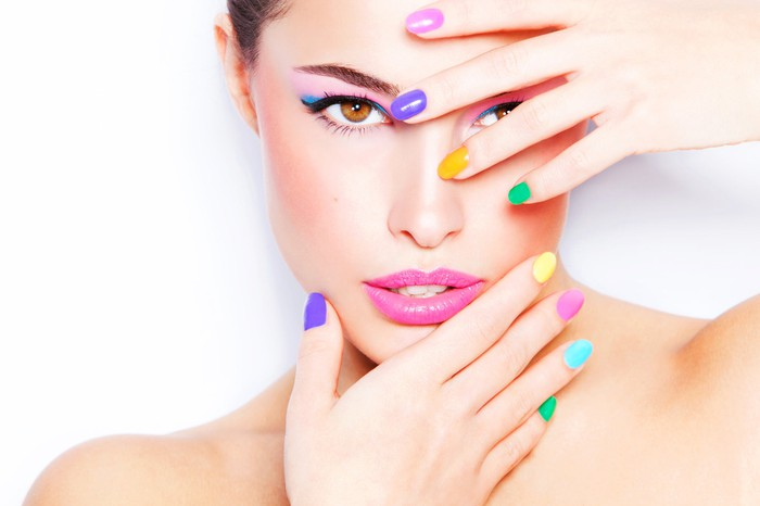 A female model wearing makeup holds her brightly-colored fingernails in front of her face.
