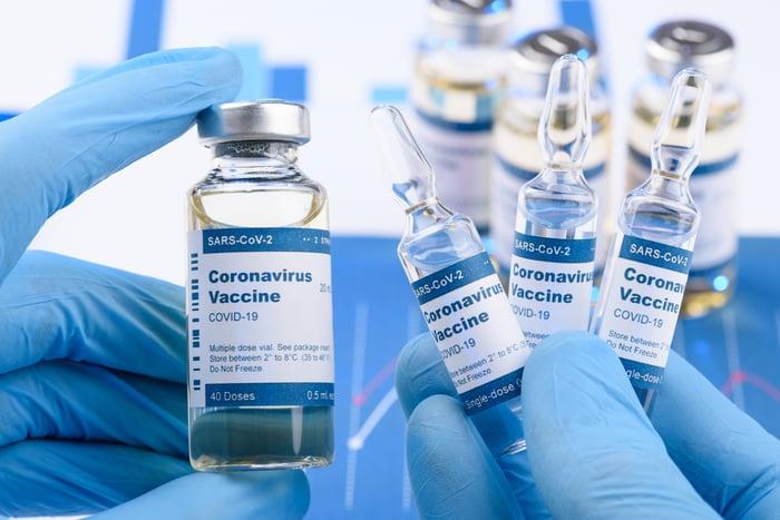 Gloved hands holding bottles labeled coronavirus vaccine.