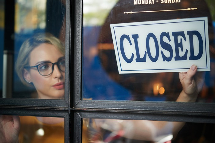 Woman hanging a CLOSED sign in a store window.