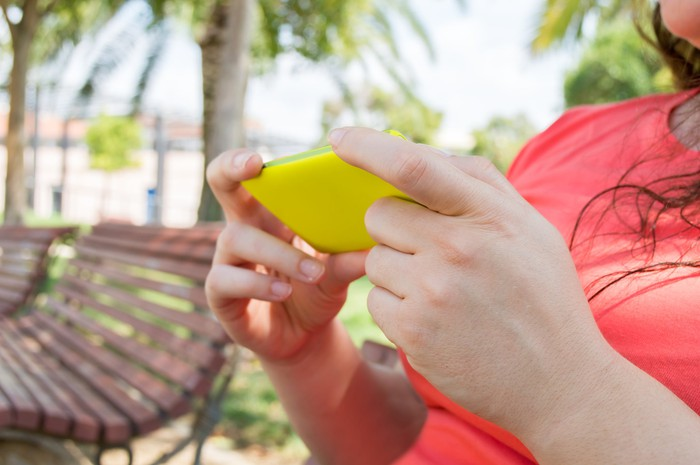 Close up of a girl's hands using a phone in an outdoor environment.
