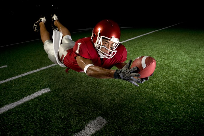 A football player leaping for a catch during a night game.
