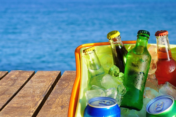 A cooler filled with bottled and canned drinks on a wooden dock with a body of water in the background