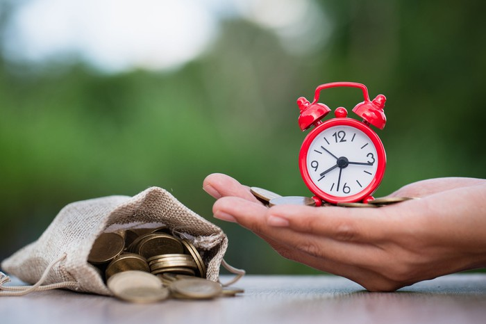 A hand holding a small alarm clock next to a bag full of coins on a table