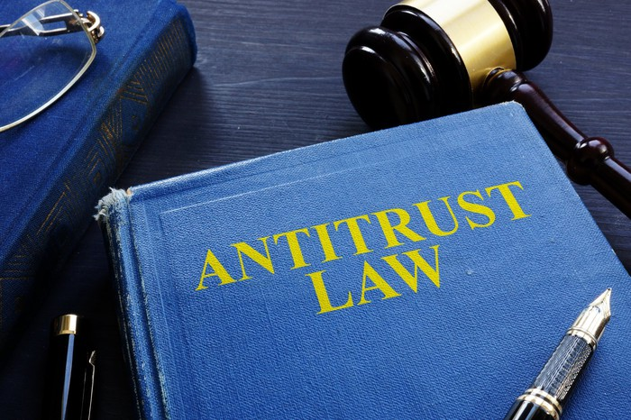 A book titled Antitrust Law with a gavel next to it and a fountain pen on top of it.
