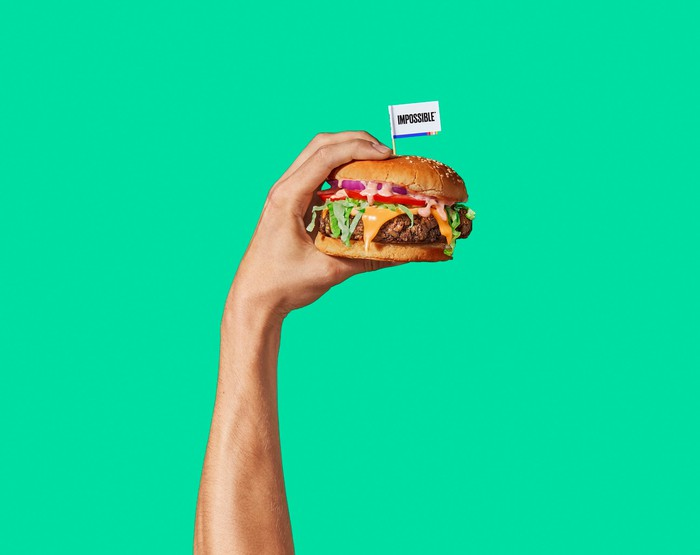Person holding an Impossible Burger sandwich.