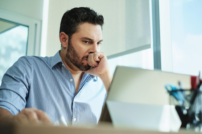 Worried man sitting, looking at a computer screen.