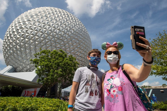 mother and son in protective face masks taking selfie in front of Epcot Center ball