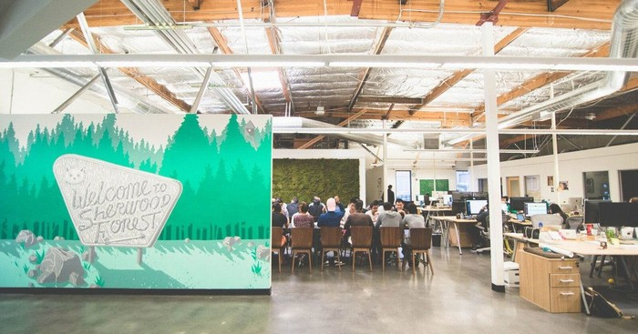 Office space with a green backdrop and a group of about a dozen people sitting around a conference table.
