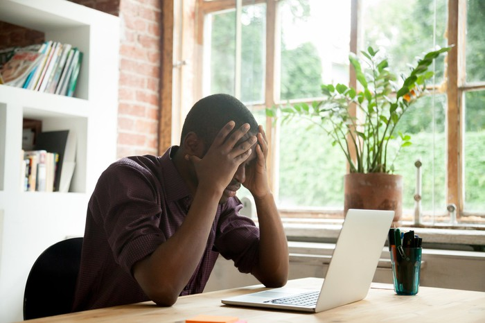 Man at laptop holding his head