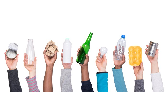 Nine hands holding up various cans, jars, bottles, and containers, along with crumpled packing paper and a lightbulb