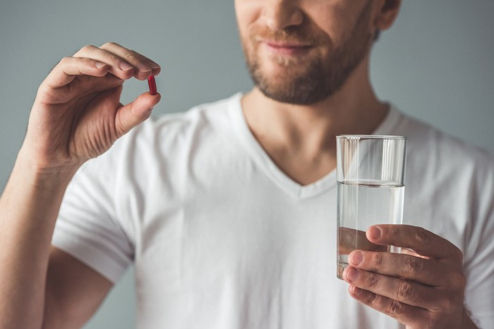 Man holding pill in one hand and glass of water in other hand