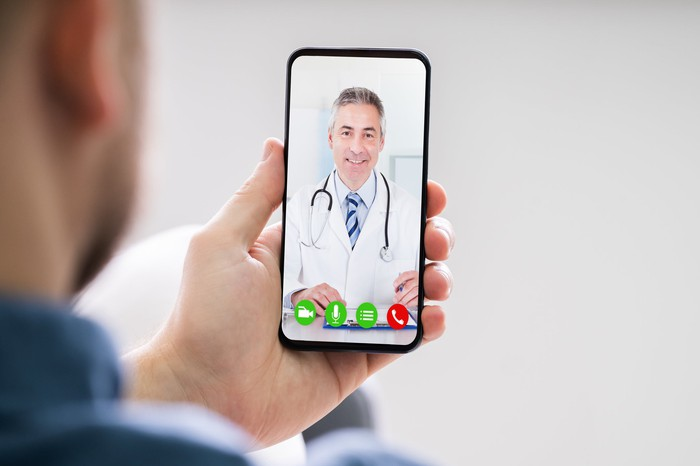 Man's hand holding a cell phone with a doctor on screen.