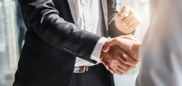 Two people shaking hands on a deal.