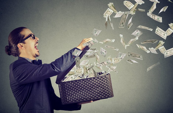 A man holds an open suitcase as dollar bills fly away.
