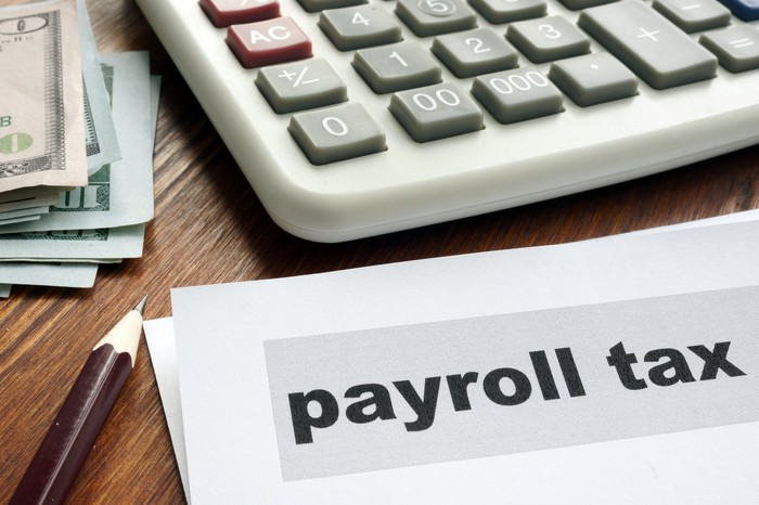 Document with the words payroll tax on it sitting on wooden surface next to pencil, calculation, and bills