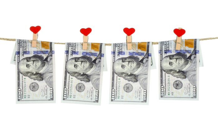 $100 bills hung on a string by close pins with hearts on them.