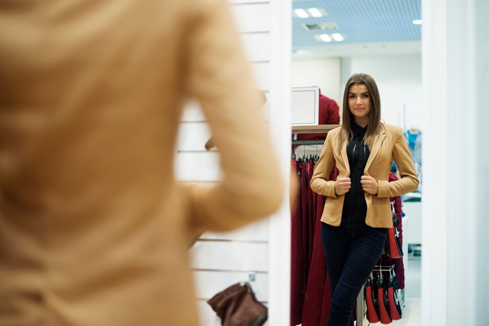 Woman trying on a jacket.