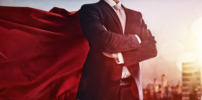A man fromt he neck down in a business suit and a cape coming out the back.