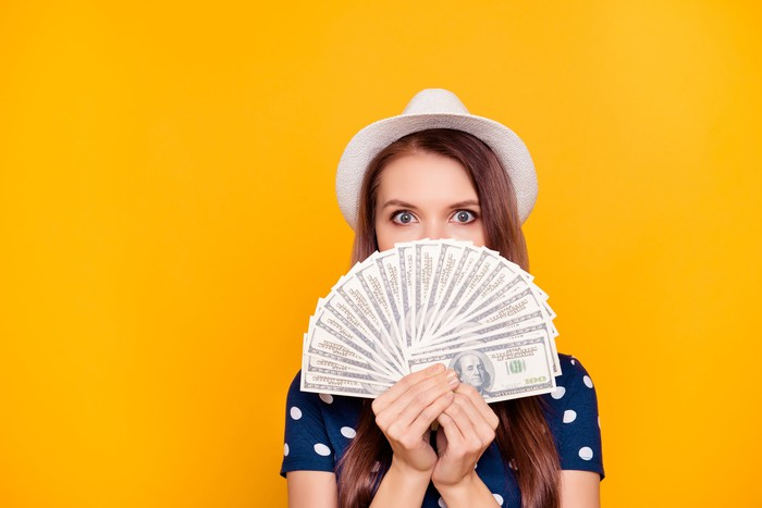 Person wearing hat holding a fanned-out set of $100 bills in front of mouth and shoulders.