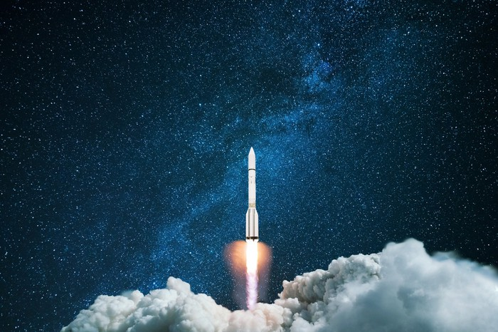 A rocket launches in front of a starry background.